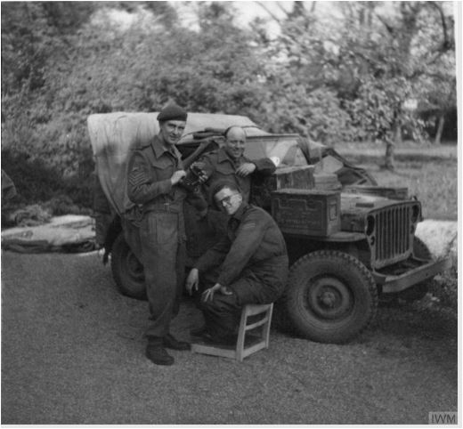 AFPU personnel, Dick Gee, 'Tubby' Palmer and Sergeant Eddy Smales posing in front of the unit Jeep at Enschede, Netherlands, May 1945..JPG